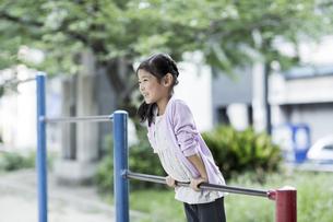 鉄棒で遊ぶ女の子の写真素材 [FYI02666834]