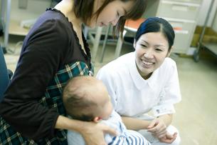 赤ちゃんをあやす看護師の写真素材 [FYI02666863]