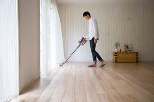 リビンングで掃除機をかける男性の写真素材 [FYI02667115]