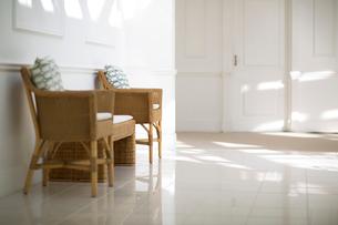 陽射しの入る白い部屋にある藤の椅子の写真素材 [FYI02667160]