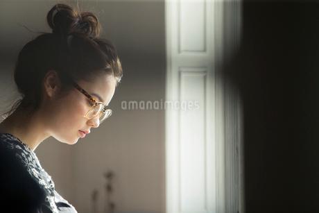 窓際で俯くお団子ヘアーの20代女性の写真素材 [FYI02667351]