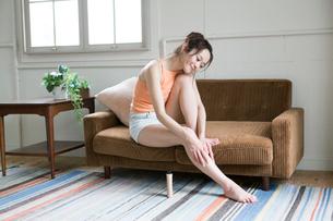 ソファに座りボディクリームを塗る30代女性の写真素材 [FYI02667361]
