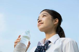 青空の下ペットボトルを持ち微笑む女子高校生の写真素材 [FYI02667379]