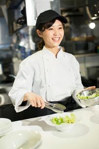 調理場で働く笑顔の20代女性の写真素材 [FYI02667383]