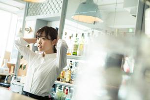髪の毛を縛る20代カフェ店員の写真素材 [FYI02667388]