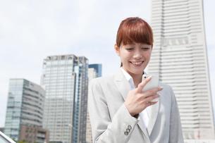 携帯電話を見るヤングビジネスウーマンの写真素材 [FYI02667392]