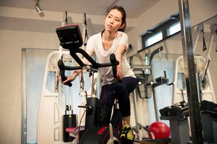 音楽を聴きながらエアロバイクを漕ぐ20代女性の写真素材 [FYI02667453]