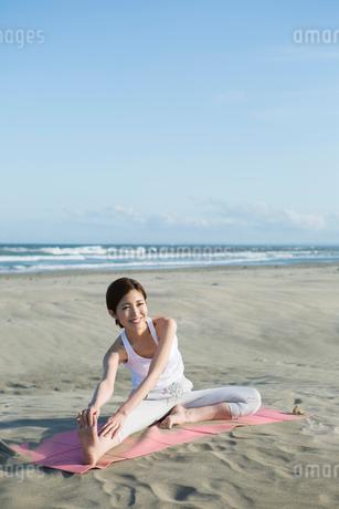 浜辺でヨガをする20代女性の写真素材 [FYI02667462]