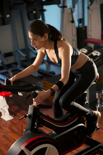エアロバイクを漕ぐ20代女性の写真素材 [FYI02667486]