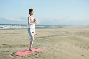 浜辺でヨガをする20代女性の写真素材 [FYI02667494]