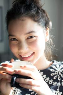 コーヒーカップを持つ笑顔の20代女性の写真素材 [FYI02667500]