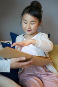 本を指差す笑顔の女の子の写真素材 [FYI02667505]