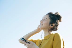 青空の下音楽を聴く20代女性の写真素材 [FYI02667539]