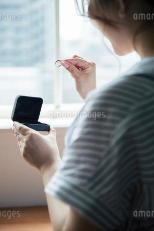 指輪ケースから指輪を取り出す女性の後ろ姿の写真素材 [FYI02667548]