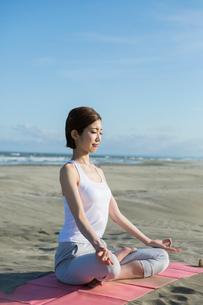 浜辺でヨガをする20代女性の写真素材 [FYI02667555]
