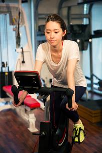 音楽を聴きながらエアロバイクを漕ぐ20代女性の写真素材 [FYI02667571]