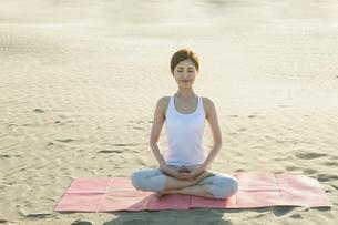 浜辺でヨガをする20代女性の写真素材 [FYI02667643]