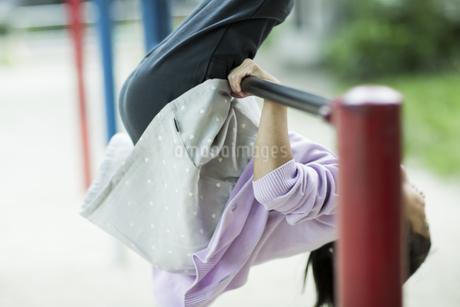 鉄棒で遊ぶ女の子の写真素材 [FYI02667730]