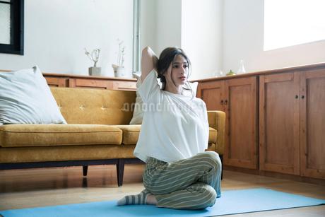 部屋でヨガのポーズをする20代女性の写真素材 [FYI02667744]