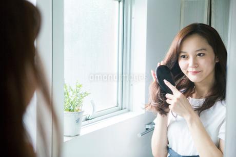 髪の毛にブラシを入れる30代女性の写真素材 [FYI02667757]