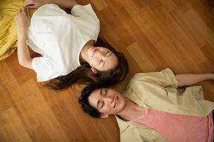 床に寝転がり目を閉じる笑顔の20代カップルの写真素材 [FYI02667761]