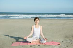 浜辺でヨガをする20代女性の写真素材 [FYI02667767]
