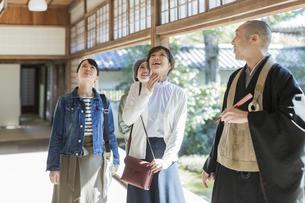 寺院を案内する住職と3人の女性の写真素材 [FYI02667919]