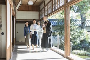 寺院を案内する住職と3人の女性の写真素材 [FYI02667929]