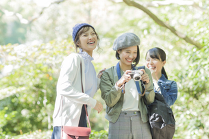 カメラを持って笑顔の3人の女性の写真素材 [FYI02668040]