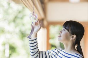 風鈴に触れる若い女性の写真素材 [FYI02668165]