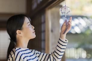 風鈴に触れる若い女性の写真素材 [FYI02668210]