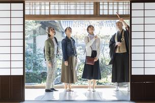 寺院を案内する住職と3人の女性の写真素材 [FYI02668258]