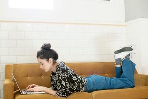ソファに寝転びパソコンを操作する20代女性の写真素材 [FYI02668470]