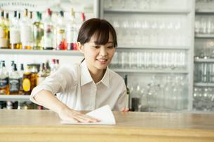 テーブルを拭く20代カフェ店員の写真素材 [FYI02668480]