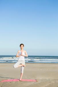 浜辺でヨガをする20代女性の写真素材 [FYI02668499]