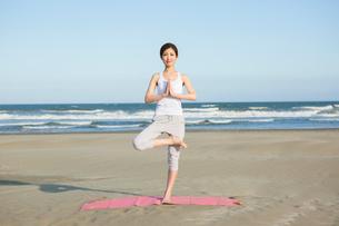 浜辺でヨガをする20代女性の写真素材 [FYI02668571]