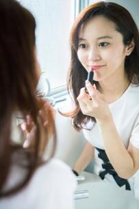 口紅を塗る30代女性の写真素材 [FYI02668573]