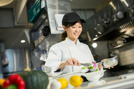 調理場で働く笑顔の20代女性の写真素材 [FYI02668604]
