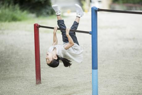 鉄棒で遊ぶ女の子の写真素材 [FYI02668605]