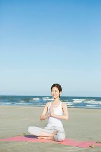 浜辺でヨガをする20代女性の写真素材 [FYI02668654]