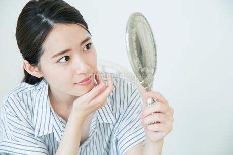 鏡を持ち肌に手を当て状態を確かめる20代女性の写真素材 [FYI02668694]