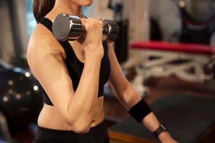 ダンベルを持ちトレーニングをする女性の写真素材 [FYI02668716]