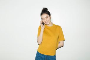 電話をする笑顔の20代女性のポートレートの写真素材 [FYI02668733]