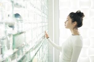 おしゃれな壁に手を当てる20代女性の写真素材 [FYI02668745]