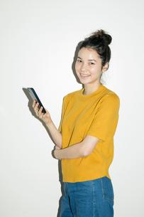 スマホを持つ笑顔の20代女性ポートレートの写真素材 [FYI02668764]