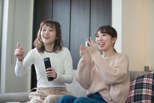 テレビを見る笑顔の20代女性2人の写真素材 [FYI02668835]