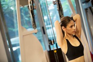 ダンベルを持ちトレーニングをする20代女性の写真素材 [FYI02668841]