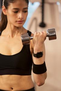ダンベルを持ちトレーニングをする20代女性の写真素材 [FYI02668854]