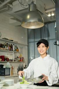 調理場で働く笑顔の20代女性の写真素材 [FYI02668997]