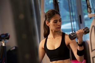 ダンベルを持ちトレーニングをする20代女性の写真素材 [FYI02669032]